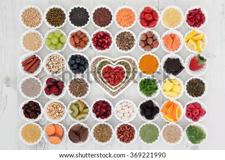 Large superfood selection in porcelain crinkle bowls and heart shaped dishes over distressed wooden background. High in vitamins and antioxidants. - stock photo