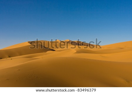 Large sweeping dunes in Sahara Desert during a clear day - stock photo
