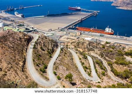 large tankers in a port next to a mountain - stock photo