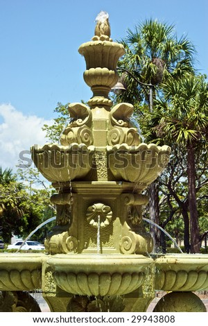 large tiered public water fountain with palm trees and many spouts
