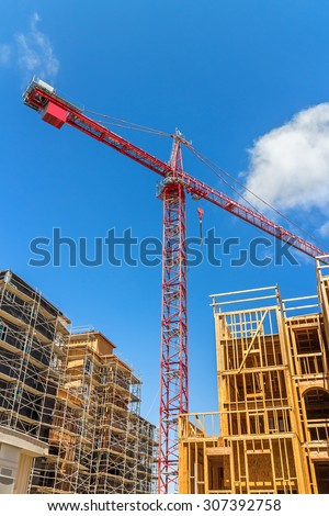 Large tower crane and new unfinished residential townhouse construction, tilted buildings perspective. Urban development theme. Blue sky and cloud background. Vertical composition.    - stock photo