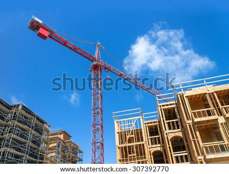 Large tower crane and new unfinished residential townhouse construction, tilted buildings perspective. Urban development theme. Blue sky and cloud background.  - stock photo