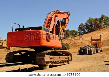 Large track excavator being delivered to a construction site on a low-boy trailer and truck