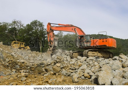 Large track hoe excavator digging out old rock during preparation at a new commercial development road construction project - stock photo