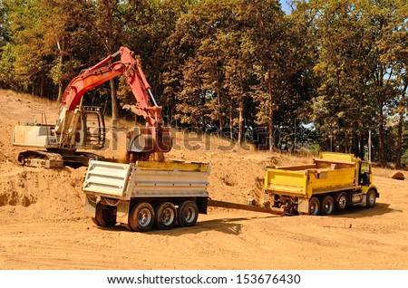 Large track hoe excavator removing top soil and loading into a tandem dump truck at a new commercial development construction site