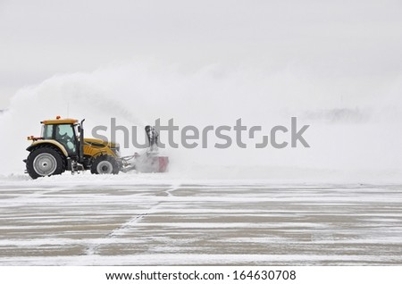 large tractor with snow plow at work during a winter storm - stock photo