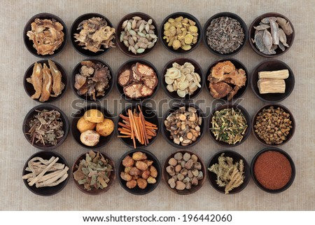 Large traditional chinese herbal medicine selection in wooden bowls. - stock photo