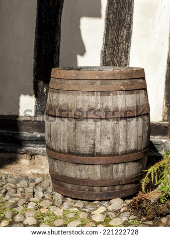 Large traditional oak barrel standing alone in a courtyard. - stock photo