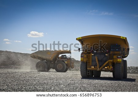Large trucks transport gold ore from open cast mine. Barrick Cowal Gold Mine in New South Wales, Australia.