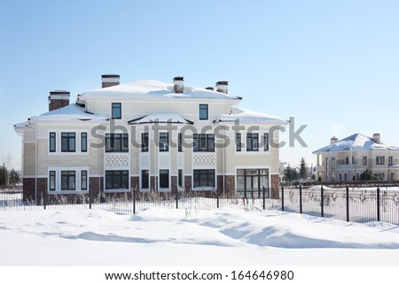 Large two-storey new cottage with big windows on sunny frosty winter day. - stock photo