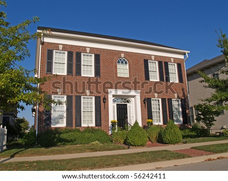 Large two story new brick home built to look like an old historical home. - stock photo