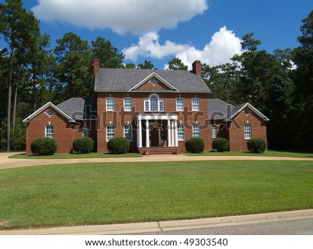 Large two story red brick residential home with side entry garage. - stock photo