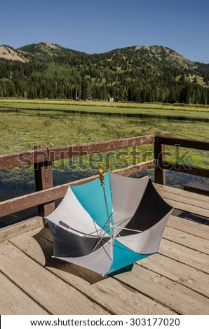 Large umbrella used to block the sun on a bright, sunny day was casually tossed aside on an observation deck - stock photo
