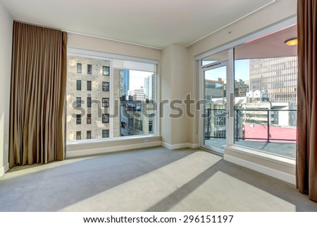 Large unfurnished bedroom with fireplace, and large windows.