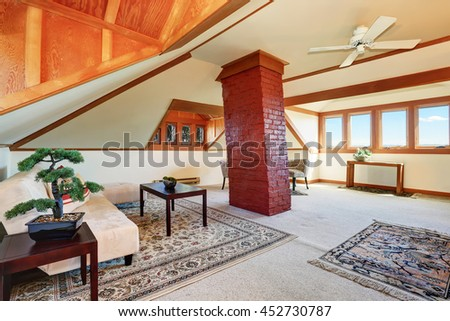 Large upstairs living room with cozy sitting area. There is high vaulted ceiling with brown trim and nice rugs.