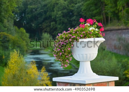 Large vase with flowers on a background of forest and river.