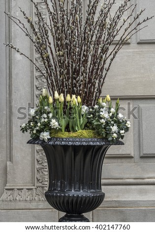 Large vase with spring flowers in front of building - stock photo