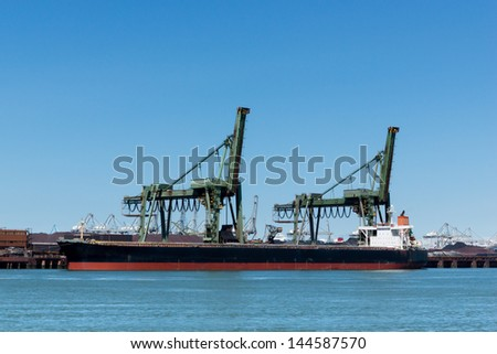 Large vessel unloading its iron ore cargo - stock photo