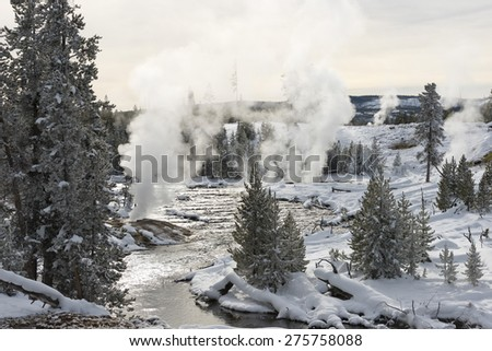 Large view of steaming geysers in a snow-covered landscape with conifers and river. Yellowstone National Park. - stock photo