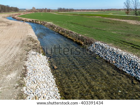 Large view on the small stream close to the green field - stock photo