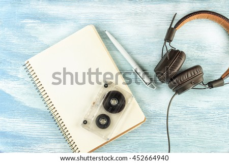 Large Vintage Leather headphones to play music lie next to a blank notebook with a ballpoint pen and audio tape on blue wooden background. Mock up. Top view. Flat lay. - stock photo