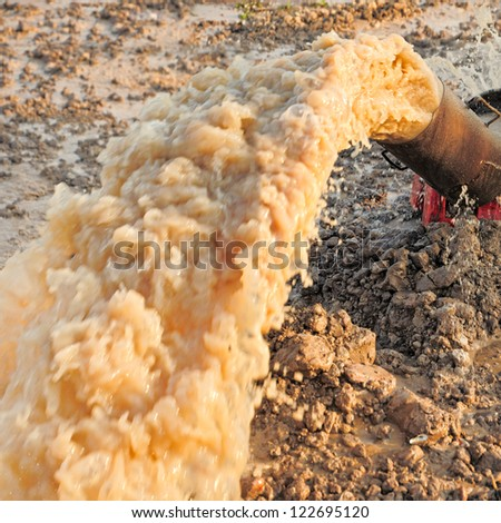 Large water pump gushing from an old rusty pipeline. - stock photo