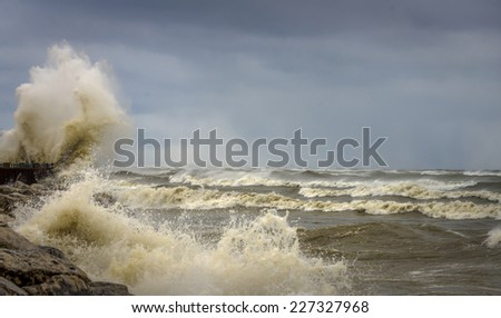 Large wave spraying in the air on shore of Lake Michigan - stock photo
