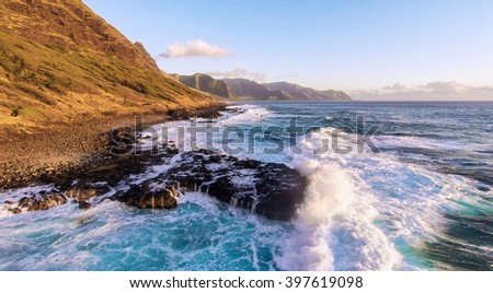 Large waves crashing into rocky outcrop along a mountain side trail on the north west shore on the island of Oahu in the Hawaii Islands - stock photo