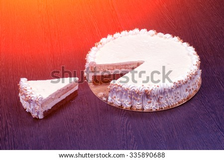 Large white cake with a piece cut off - stock photo