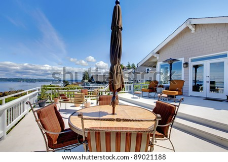 Large white house terrace with water view during summer. - stock photo