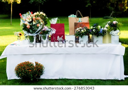 large white table with flowers and gift packages in the park