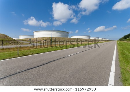 large white tanks for petrol and oil in the Rotterdam harbor next to a road - stock photo