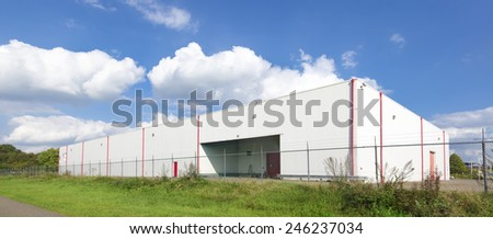 large white warehouse against a nice cloudy sky - stock photo