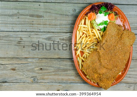 Large Wiener Schnitzel on a clay plate with fries - stock photo