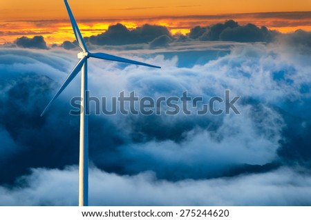 Large wind turbine standing against a stormy cloudy background at sunset. - stock photo