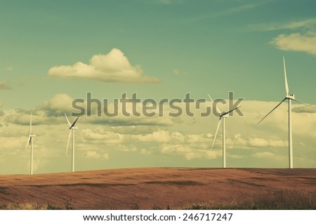Large wind turbines gathering electricity out of the wind in eastern Colorado, USA. Retro instagram look.