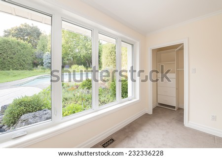 Large window in empty bedroom looking on summer backyard with garden and residential pool