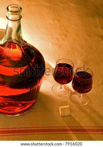 Large wine bottle and glasses on homespun tablecloth