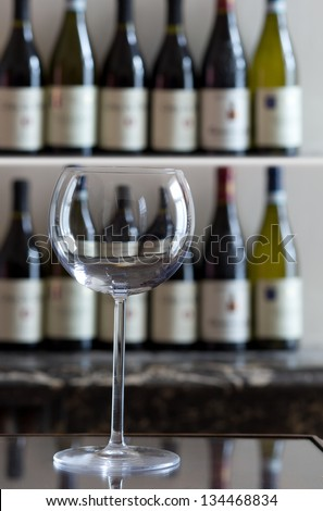 Large wine glass with bottles of wine in the background - stock photo