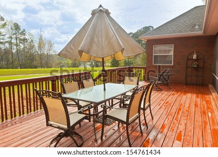 Large wooden backyard deck with patio furniture and a view of lake - stock photo