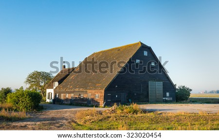 Large wooden barn with tiled roof and an old whitewashed house with thatched roof in a polder in the Netherlands. The buildings date back to the year 1900. - stock photo