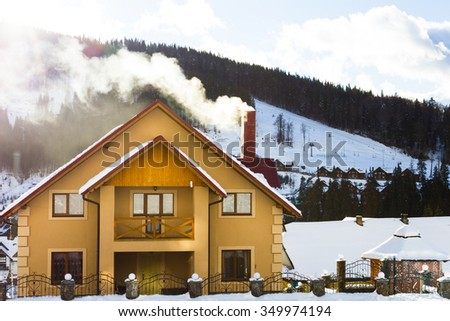 Large yellow house with a smoking chimney in the mountains - stock photo