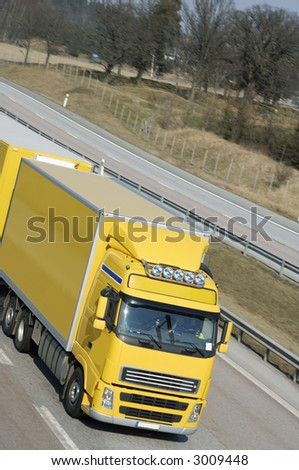 large yellow truck driving, elevated-view, close-up of cabin - stock photo