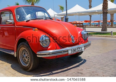 LARNACA, CYPRUS - JUL 15: Vintage red Volkswagen VW Beetle car (Volkswagen Type 1, Volkswagen Bug) parked near the Finikoudes Beach (Larnaca Promenade) on July 15, 2013 in Larnaca, Cyprus. - stock photo