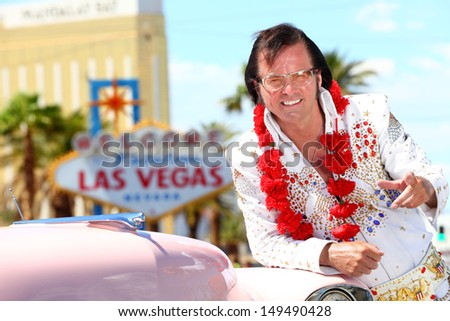 Las Vegas Elvis impersonator on the strip pointing looking at camera in front of Welcome to Fabulous Las Vegas sign and car. - stock photo
