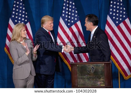 LAS VEGAS - FEB 2: Mitt Romney (R) shakes hands with Donald Trump as Romney's wife, Ann Romney, watches at the Trump Hotel on February 2, 2012 in Las Vegas, Nevada. Trump is endorsing Romney for president. - stock photo