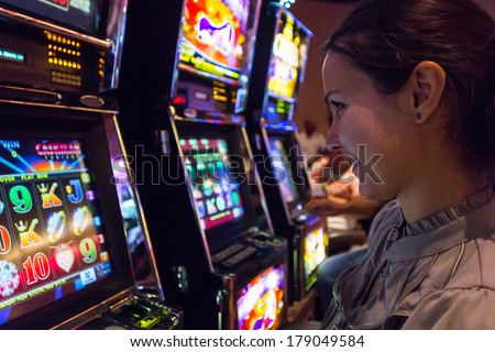 LAS VEGAS - JULY 13, 2013: Concentrated girl playing slot machines in The Quad Resort and Casino. - stock photo