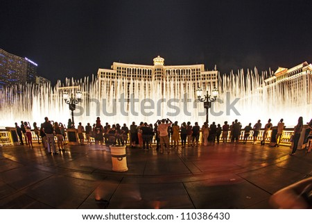 LAS VEGAS - JUNE 15: people watch the famous fountain show at Las Vegas Bellagio Hotel Casino at night on June 15, 2012 in Las Vegas, Nevada. - stock photo