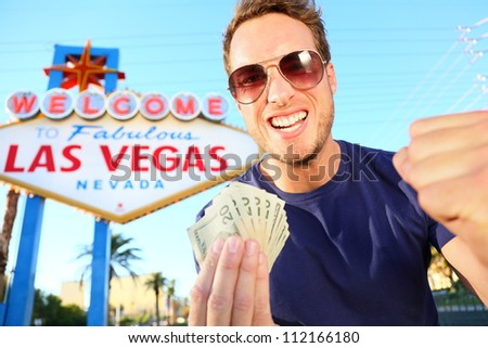 Las Vegas man winning money. Winning gambler standing excited in front of Welcome to Fabulous Las Vegas sign. - stock photo