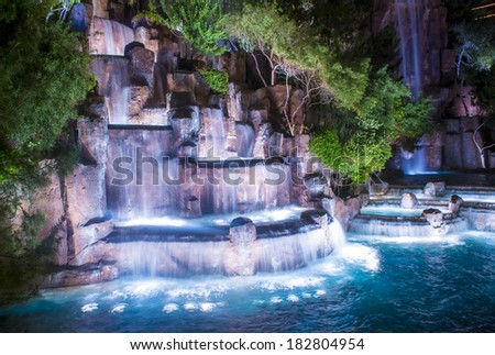 LAS VEGAS - MARCH 15 : Waterfall in front of the entrance to the Wynn Hotel and Casion on March 15, 2014 in Las Vegas. The hotel has 2,716 rooms and it opened in 2005. - stock photo